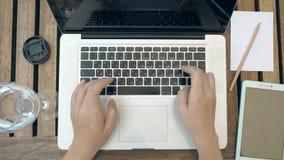 Una persona sta scrivendo sul suo computer portatile Vista superiore POV archivi video