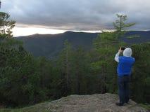 Una persona toma una puesta del sol en las montañas de Buriatia Imagen de archivo