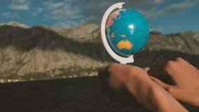 Una persona tuerce el globo y elige el lugar del viaje siguiente almacen de metraje de vídeo