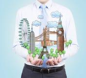Una persona in vestiti convenzionali tiene in sue mani uno schizzo dei posti famosi da ogni parte del mondo Fotografia Stock