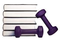 Una pesa de gimnasia y una pila de libros para el concepto de aprendizaje ser cabido y sano Imagenes de archivo