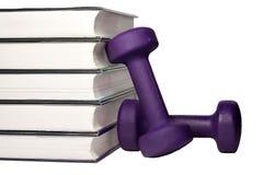 Una pesa de gimnasia y una pila de libros para el concepto de aprendizaje ser cabido y sano Fotografía de archivo