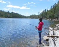 Una pesca de la chica joven en un lago de la montaña Imagen de archivo