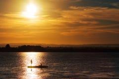 Una pesca dei due pescatori sul lago al tramonto Fotografie Stock