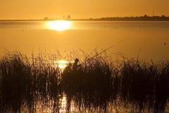 Una pesca dei due pescatori sul lago al tramonto Immagini Stock
