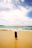 Una pesca del muchacho en la playa imagenes de archivo