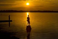 Una pesca di due pescatori della siluetta Fotografie Stock
