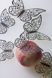Una pesca succosa matura si trova su una superficie bianca Tutt'intorno è decorato con il taglio delle farfalle da stagnola Fotografia Stock Libera da Diritti