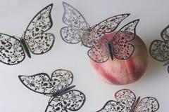 Una pesca succosa matura si trova su una superficie bianca Tutt'intorno è decorato con il taglio delle farfalle da stagnola Fotografia Stock
