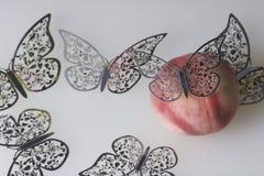 Una pesca succosa matura si trova su una superficie bianca Tutt'intorno è decorato con il taglio delle farfalle da stagnola Fotografie Stock