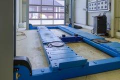 Una piattaforma elevatrice in un'officina riparazioni dell'automobile fotografie stock