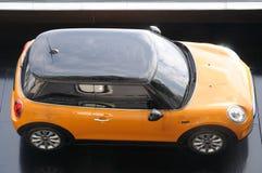 Una piccola automobile della porta di giallo due immagine stock