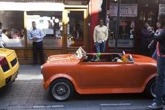 Una piccola automobile rossa sta sul vicolo del mattone della via La gente cammina sul vicolo del mattone prende le immagini dell Fotografia Stock