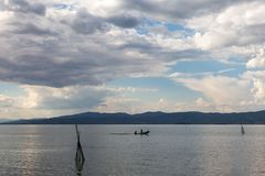 Una piccola barca con qualche gente su un lago, sotto un bello bl Immagini Stock Libere da Diritti