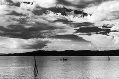 Una piccola barca con qualche gente su un lago, sotto un bello, d Fotografie Stock Libere da Diritti
