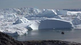 Una piccola barca naviga lungo gli iceberg enormi video d archivio