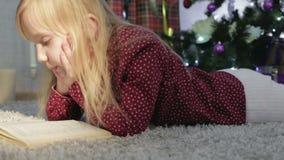 Una piccola bella ragazza che legge un libro sotto l'albero di Natale stock footage