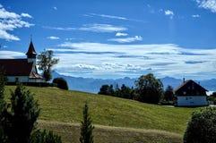 Una piccola cappella su una collina, sulle montagne e sul cielo blu fotografie stock