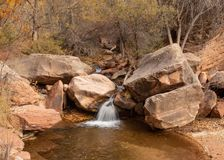 Una piccola cascata sul sottopassaggio sinistro della forcella nel parco di Zion National versa sopra i massi dell'arenaria fotografia stock