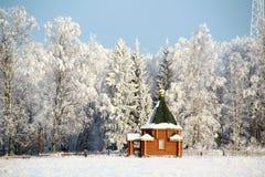 Una piccola chiesa in una foresta di inverno Immagini Stock Libere da Diritti