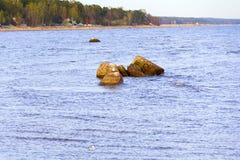 Una piccola cresta di pietra sull'acqua fotografia stock