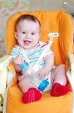 Una piccola età sorridente del ragazzo di 7 mesi con il biberon Immagini Stock Libere da Diritti
