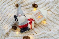 Una piccola figura di Santa Claus con un regalo e le luci di Natale Fotografia Stock Libera da Diritti