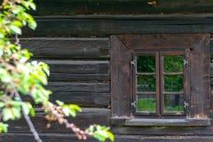 Una piccola finestra nella parete di vecchia casa di legno immagine stock libera da diritti
