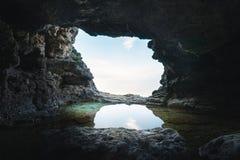 Una piccola grotta con uno stagno di riflessione immagine stock