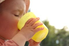 Una piccola neonata beve l'acqua da un vetro di plastica fotografie stock libere da diritti