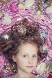 Una piccola ragazza bionda che si trova su un tessuto di seta rosa con giocattoli di Natale ghirlanda e di Natale intorno lei cap Fotografia Stock