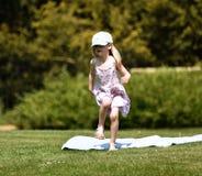Una piccola ragazza bionda, circa 4 anni, in un berretto da baseball dell'arcobaleno balla nel sole ad un picnic in un parco Il R fotografia stock