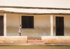 Una piccola ragazza cammina sulla parete della scuola nel Kenya Immagini Stock Libere da Diritti