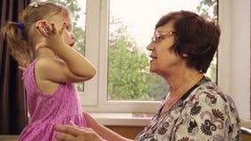 Una piccola ragazza di due anni gioca con sua nonna stock footage