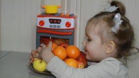 Una piccola ragazza dolce le mostra l'amore di frutta Il bambino si siede ad una tavola e mangia i mandarini, le arance e le mele stock footage