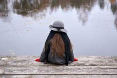 Una piccola ragazza graziosa che si siede su un ponte immagine stock