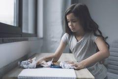 Una piccola ragazza mora rastrella in un mucchio delle cose che si trovano su una piccola tavola che sta vicino alla finestra Fotografia Stock Libera da Diritti