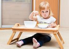 Una piccola ragazza sta mangiando fotografie stock