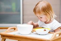 Una piccola ragazza sta mangiando fotografia stock