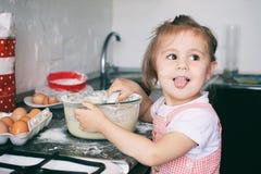 Una piccola ragazza sveglia che prepara la pasta nella cucina a casa fotografia stock libera da diritti