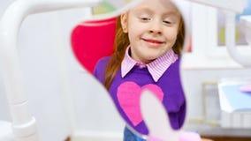 Una piccola ragazza sveglia con capelli rossi ammira i suoi denti sani nello specchio che si siede nella sedia dentaria video d archivio
