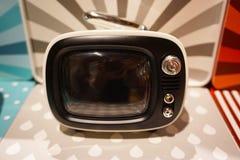 Una piccola televisione in un fondo variopinto immagini stock