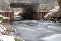 Una piccola torrente nell'inverno Un fiume che scorre sotto un ponte concreto fotografia stock libera da diritti