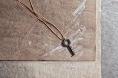 Una piccola vecchia chiave si trova su un bordo di legno Immagini Stock