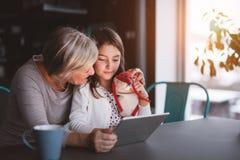 Una piccole ragazza e nonna con la compressa a casa Immagine Stock