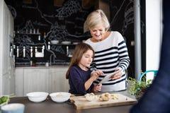 Una piccole ragazza e nonna con la compressa che cucinano a casa Immagine Stock