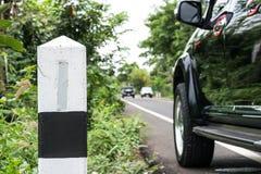 Una piedra del kilómetro en la carretera nacional con el fondo del coche imagen de archivo