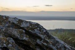 Una piedra en una alta montaña Puesta del sol fotografía de archivo