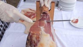Una pierna delantera del jamón de Serrano trazó en un soporte de madera con el cocinero metrajes