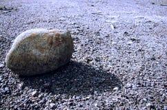 Una pietra grigia sola getta un'ombra Immagini Stock Libere da Diritti